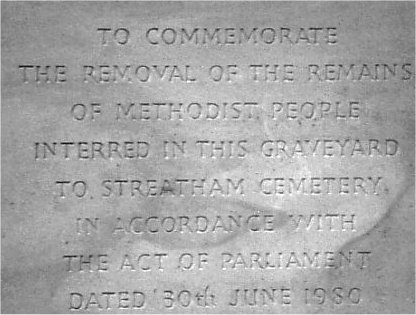A tablet in the wall facing the obelisk commemorating the removal of remains to Streatham Cemetery | John L. Symonds, 1989